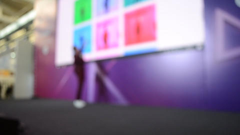 Man stands on stage. Blurred background large screen stage many people Live Action