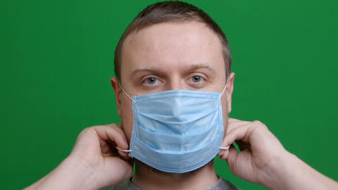 Close-up. Man puts on a protective medical mask. In the panic of the epidemic Live Action