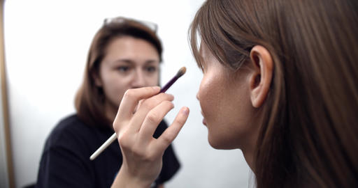 professional makeup artist applying makeup on models face before fashion show Live Action