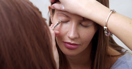professional makeup artist making eye-makeup for young model Live Action