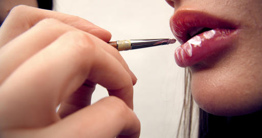 makeup artist works with the model, applies lipstick with a brush on the lips of Live Action