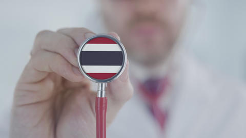 Doctor holds stethoscope bell with the Thai flag. Healthcare in Thailand Live Action