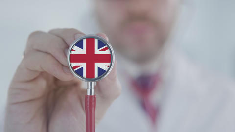 Doctor listening with the stethoscope with flag of the UK. British healthcare Live Action