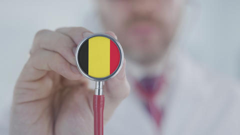 Doctor listening with the stethoscope with flag of Belgium. Belgian healthcare Live Action