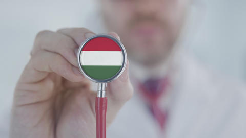 Physician uses stethoscope with the Hungarian flag. Healthcare in Hungary Live Action