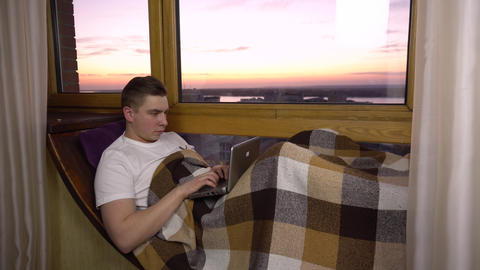 A young man is typing on a laptop. A man lies on a window sill by the window Live Action