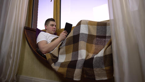 A young man is texting on the tablet. A man lies on a window sill by the window Live Action