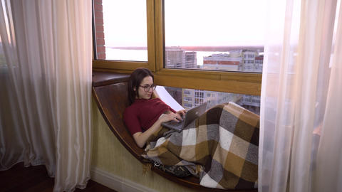 A young woman is typing on a laptop. A girl lies on a window sill by the window Live Action