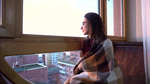 A young woman is sitting by the window. A woman sits on a windowsill wrapped in Live Action