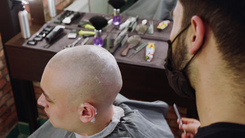 Barber shaving bald man with straight blade in barbershop. Hipster man getting Live Action