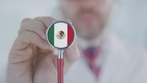 Doctor holds stethoscope bell with the Mexican flag. Healthcare in Mexico Live Action