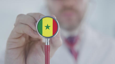 Doctor uses stethoscope with the Senegalese flag. Healthcare in Senegal Live Action