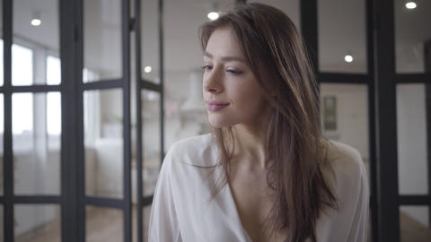 Close-up of thoughtful young Caucasian woman sitting indoors and looking around Live Action