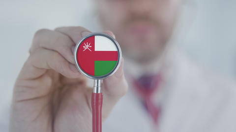Medical doctor holds stethoscope bell with the Omani flag. Healthcare in Oman Live Action