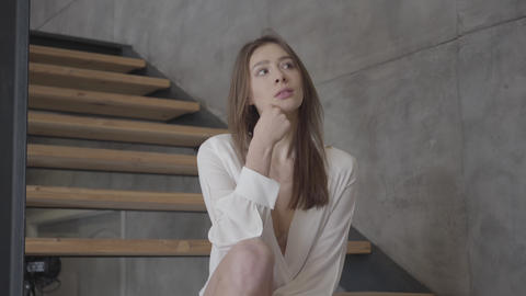 Portrait of young brunette Caucasian woman sitting on stairs indoors and Live Action