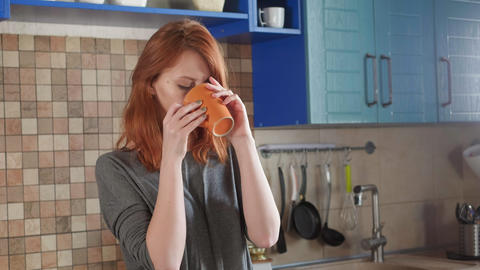 Attractive girl with red hair drinks morning coffee in the home kitchen Live Action