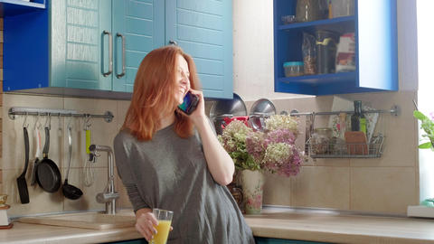 Attractive young redhead girl drinks orange juice at the weekend in the kitchen Live Action