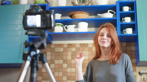 Girl food blogger influencer is recording a video or podcast in the kitchen Live Action