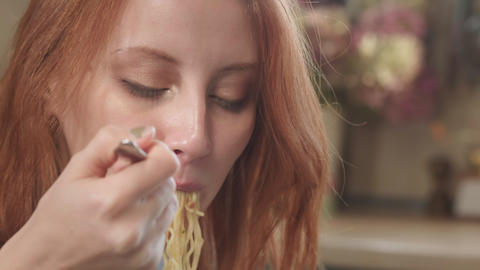Attractive redhead girl eats instant noodles with a fork in the kitchen. Eats Live Action