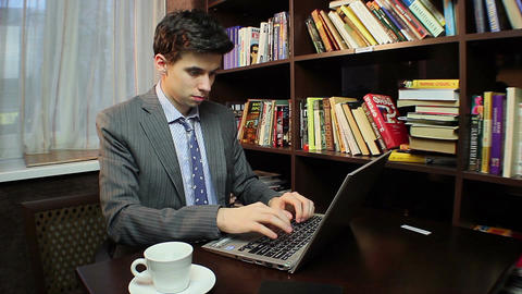 Freelancer works on computer, typing message, studying library Footage