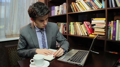 Young businessman working in library, writing down information Footage