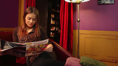 Beautiful girl having rest after long day, reading magazine Footage