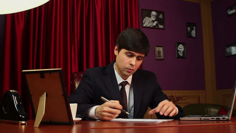 Businessman checking stock indexes, making notes, stock market Footage