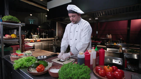 Smiling cook making sushi roll, fresh sushi ingredients on table Footage