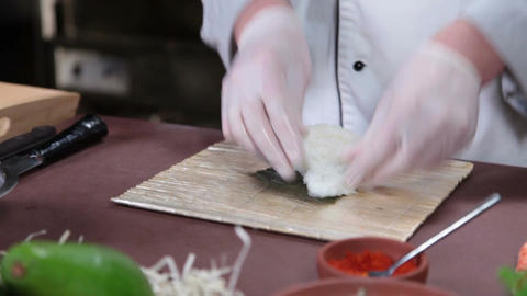 Cook making sushi rolls in kitchen, spreading rice over nori Footage