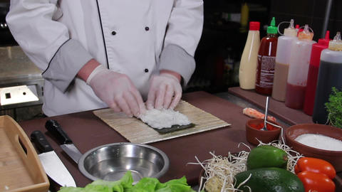 Process of making sushi rolls, cook spreading rice over nori Footage