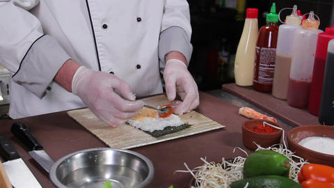 Sushi chef making sushi maki with red caviar, restaurant kitchen Footage