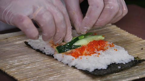 Close-up cook's hands making sushi roll with cucumber and caviar Footage