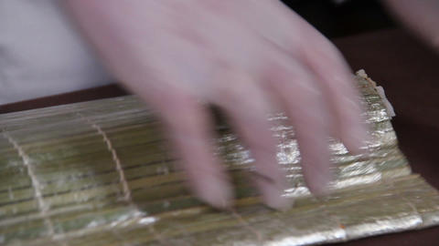 Close-up cook making Japanese sushi rolls on a bamboo mat Footage