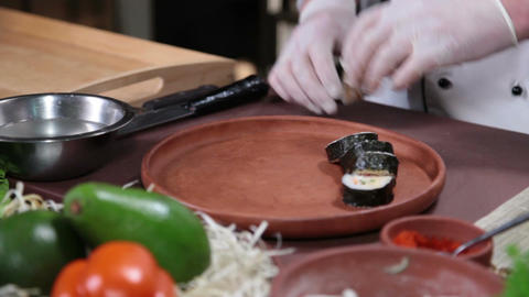 Cook serving delicious Japanese sushi rolls on a wooden plate Footage