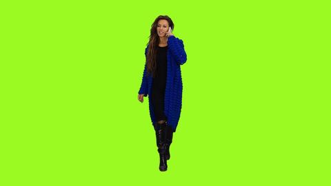Woman in blue cardigan walking & talking on smartphone, alpha channel Footage