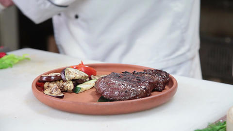 Steak gets taken off barbecue, chef presenting dish on plate Footage