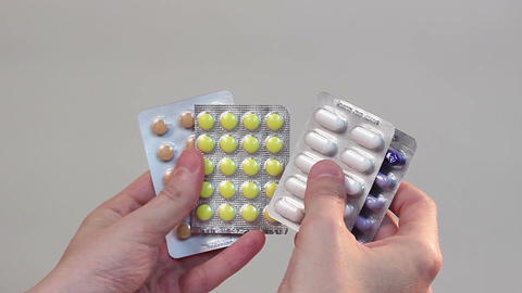 Hands holding pills in blister packs, uneasy choice, despair Footage
