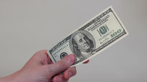 Hand holding the U.S. one hundred-dollar bill, wealth, finances Footage