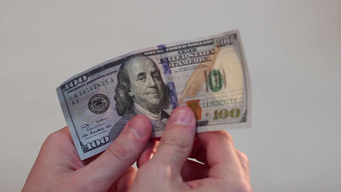 Person holding in hands and turning over one hundred-dollar bill Footage