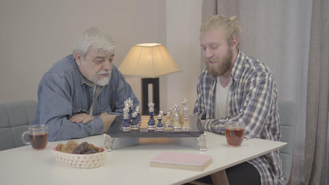 Portrait of young and senior men playing chess indoors. Caucasian adult son Live Action