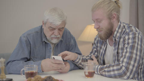 Young Caucasian man teaching senior father to use smartphone. Positive son Live Action
