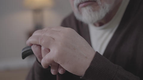 Extreme close-up of male mature Caucasian hands holding walking stick Live Action