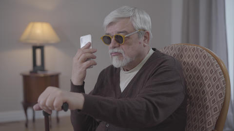Portrait of blind old Caucasian man talking on the phone indoors. Grey-haired Live Action