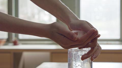 Corona pandemic - kids hands using hand sanitizer to prevent coronavirus spread Live Action