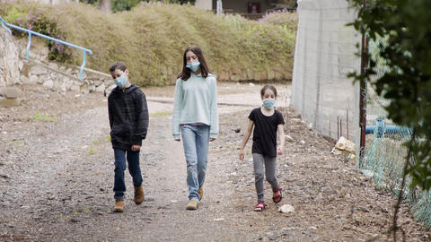 Coronavirus pandemic - kids walking outdoors with face masks to avoid contagion Live Action