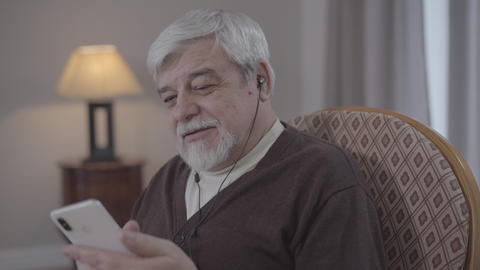 Portrait of positive mature man moving and singing as listening to music in Live Action