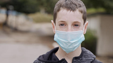 Coronavirus pandemic close up on boy face wearing face mask to avoid contagion Live Action