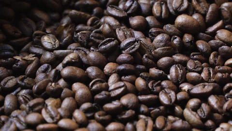 Mechanical Arm Mixes Darkly Roasted Coffee Beans on Cooling Tray Live Action