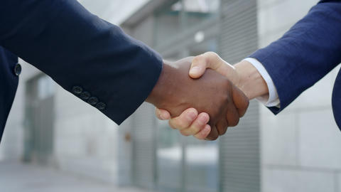 Business partners shaking hands on street. Handshake of businessmen outdoors Live Action