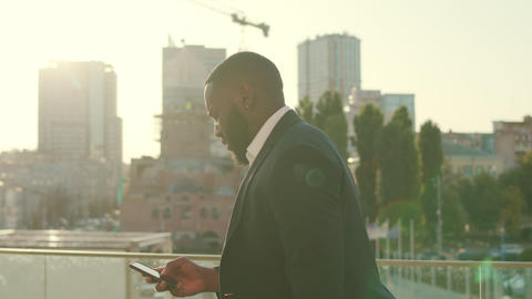 Businessman using smartphone at modern street.Employee texting on phone outdoors Live Action
